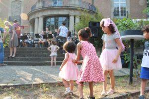 Kinder in Festtagskleidern hören der Bigband zu